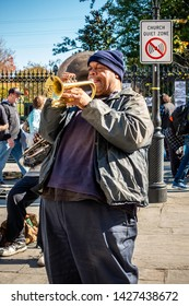 New Orleans, USA - Dec 11, 2017: A male street musician on trumpet performing a lively jazz act to entertain the public. Image captured at the iconic French Quarter, in front of Jackson Square.