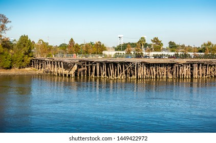 New Orleans, USA - Dec 11, 2017: Wooden jetty platform along the Mississippi River that was destroyed by Hurricane Katrina in August 2005. Image features the collapsed supporting pylons.
