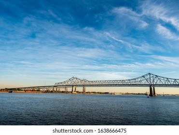 New Orleans, USA - Dec 11, 2017: View of the Crescent City Connection bridge from the Steamboat Natchez, along the Mississippi River. Orange light from the afternoon sun filters through the horizon.