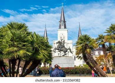New Orleans, USA - Dec 17, 2017: Commemorative statue of General Andrew Jackson on horseback in Jackson Square, with visitors around the statue. St. Louis Cathedral in the background.