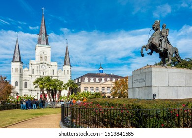 New Orleans, USA - Dec 17, 2017: Bronze commemorative statue of Andrew Jackson on horseback in Jackson Square, with visitors around the statue. St. Louis Cathedral in the background.