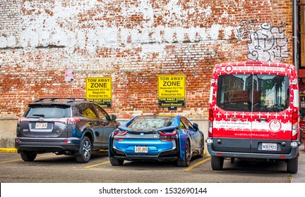 New Orleans, USA - Dec 17, 2017: Different private vehicles parked in dedicated lots in the GoPark parking facility along Canal Street in the iconic French Quarter. Tow away warning signs shown.