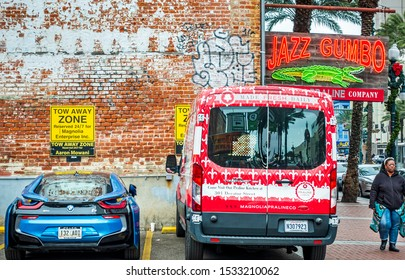 New Orleans, USA - Dec 17, 2017: Different private vehicles parked in dedicated lots in the GoPark parking facility on Canal Street in the French Quarter. Tow away warning signs shown. Lady walks by.