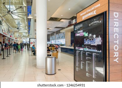 New Orleans, USA - Dec 4, 2017: Spacious interior of the Outlet Collection mall at Riverwalk. Features a large directory signboard with people around the food court area.