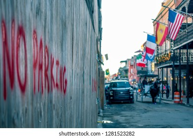 """New Orleans, USA - Dec 4, 2017: A """"No Parking"""" sign on side of alley. Very shallow depth of field image. Buildings with nostalgic architectural designs, cars and mule cart aesthetically in blur."""