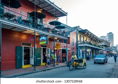 New Orleans, USA - Dec 4, 2017: Street level view along Bourbon Street in the iconic French Quarter; wrought iron balconies of pubs and cafes. People, cyclist and car on the road.