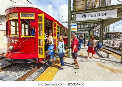 NEW ORLEANS, USA - JULY 16, 2013: people enter the  Streetcar Line in New Orleans, USA. Revamped after Hurricane Katrina in 2005, the New Orleans Streetcar line began electric operation in 1893.