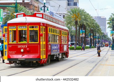 NEW ORLEANS, USA - MAY 14, 2015: Red streetcar on Canal Street, in the back another streetcar approaching and people crossing the street.