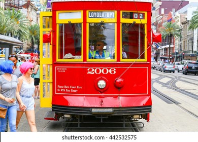 NEW ORLEANS, USA - MAY 14, 2015: Streetcar stopped on Canal Street, two women with colorful wigs crossing the street in front of it.