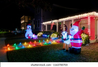 New Orleans, USA - Nov 27, 2017: Southern style American house along Fleur De Lis Drive, with lit up entrance. Night scene with Santa Claus, Reindeer and Christmas lights at the front of the house.