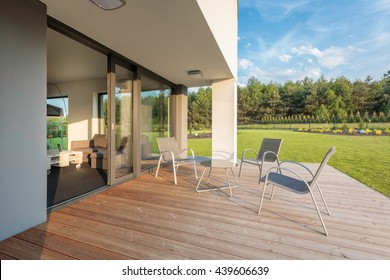 New outdoor furniture set standing on a modern patio, beautiful garden view