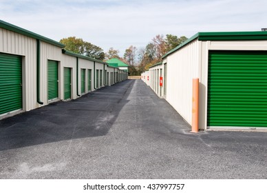 New outdoor mini storage warehouse buildings with green doors and an empty parking lot.