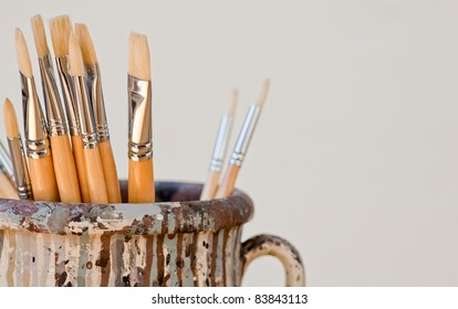 New paintbrushes in a old ceramic jar