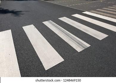 New painted crosswalk on black asphalt with nobody around.