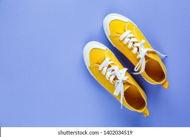 New pair of red and yellow sneakers on violet background with copy space. Lifestyle  sneaker sport shoe.