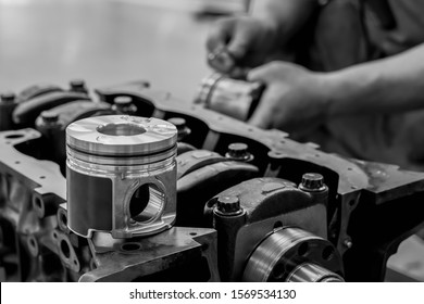New parts, pistons of cars placed on the cylinder head are awaiting replacement in the engine overhaul by a mechanic in a black and white concept garage.