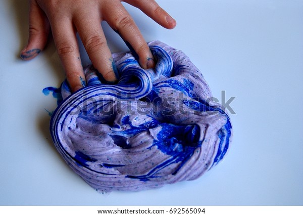 New picture of Child's hand playing with lilac slime, with blue food coloring added to it. this is a home made slime, made with borax, glue and glitter.