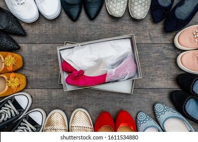 New pink ballerina shoes in box and too many old shoes on wooden background. Fashion frame of variety women shoes. Set with different types of women shoe. Fashionable Footwear Set, top view.