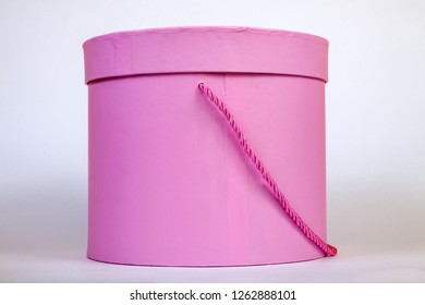 New pink cardboard box of a round form for packing a gift or flowers with a closed lid and a ribbon close-up in the background no one is.