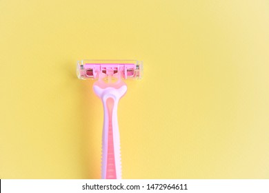 New pink disposable razors for safe shaving of female skin with selective focus on yellow background with copy space. Razor for smooth shaving. Sharp razors for personal hygienic routine