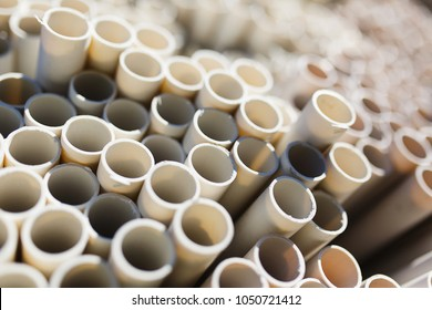 New plastic water pipes laid in a stack in the warehouse. Plumbing and water supply. Abstract background from plastic pipes. Storage and sale. Soft focus.