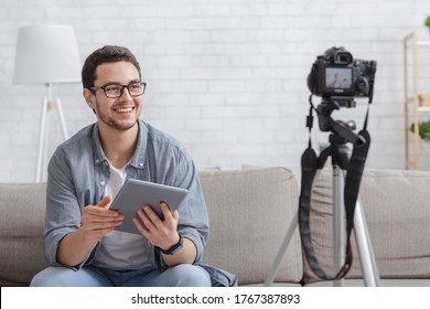 New podcast for blog. Young attractive man blogger looking at camera and talking on video shooting with devise in interior of living room on white brick wall background