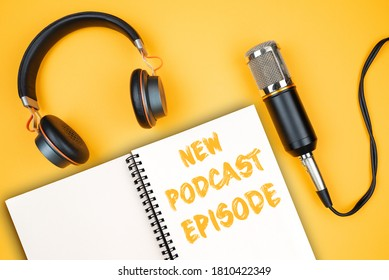 NEW PODCAST EPISODE text on notepad next to headphones and recording microphone, podcasting concept on orange background