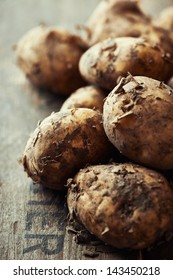 New potatoes on wooden background; close up