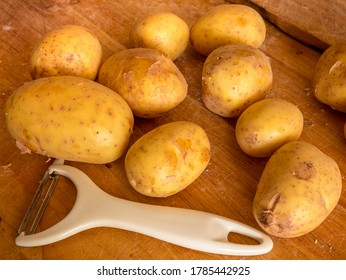 New potatoes and white peeler on a wooden worktop