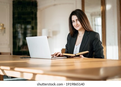 New project at work. The lawyer is sitting next to the laptop. Copy space. Accountant Manager Student beautiful brunette. A woman writes down important things. Works in a modern office.