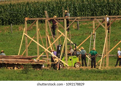 New Providence, PA, USA - July 30, 2013: A crew of Amish carpenters build a barn in the summer heat in Lancaster County.