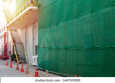 New public building with scaffolding system in under construction site during construction. Building repair and renovate. Protective net (veil) Under Constructed and Safety First Concept.