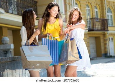 New purchase in the shop. Three attractive young women holding shopping bags and discuss their purchase outdoors. Girls are laughing and smiling and holding hands.