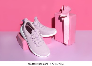 New purple sneakers, pink yoga blocks and strap on colorful background with copy space. Healthy lifestyle concept.