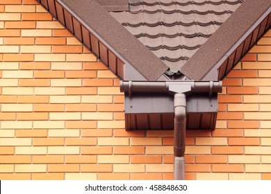 New rain gutter on a metal tiled roof with Drainage System, Stone Coated Metal tile, Plastic Siding Soffits and Eaves