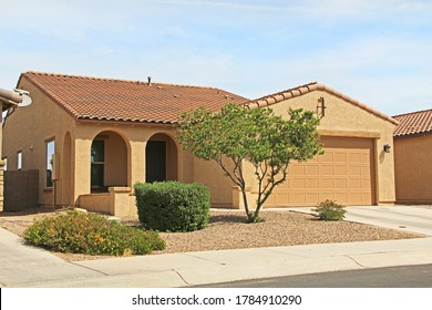 New ranch, gold and mustard yellow stucco home in Tucson, Arizona, USA with beautiful blue sky and landscaping.