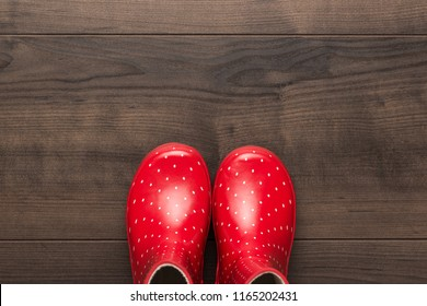 new red children's stylish gumboots on wooden floor