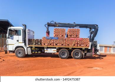 Neue rote Tonziegel auf Paletten, die von Kranich auf Lastkraftwagen und Anhänger angehoben werden, um am Baugelände am Morgen blauen Himmel geliefert zu werden.