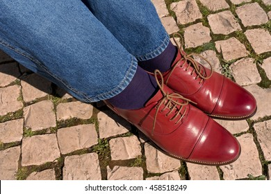 New red leather shoes on cobblestones.