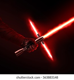 New red light saber holdng in hand close-up isolated on black. Lightsaber futuristic weapon. Sabre sword with fire force. Shiny glowing red lightsaber holding hand. Dark force warrior.