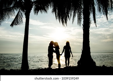 New relationship concept. Love triangle. Young man falls in love with another woman Silhouette on the seashore.