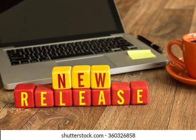 New Release written on a wooden cube in a office desk