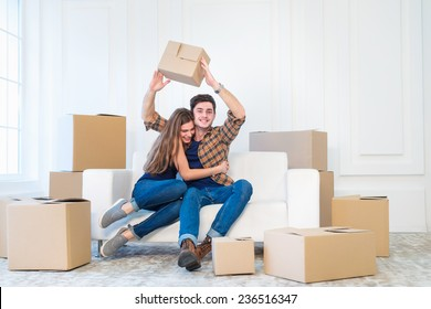 New repair and relocation. Loving couple enjoys a new apartment and keep the box in his hands while young and beautiful couple in love sitting on the couch in an empty apartment among boxes