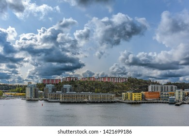 New residential apartment blocks sit on a hillside near the waterfront of Baltic sea bay in the Kvarnholmen district of Stockholm, Sweden at sunny spring morning.