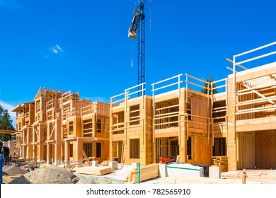 New residential building under construction with the crane about. Low rise wooden framework of the building on concrete base