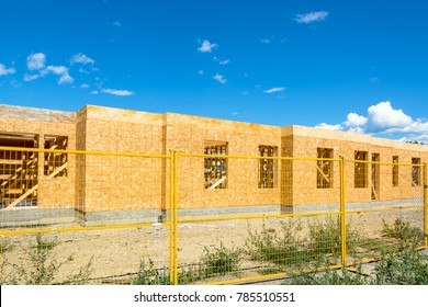 New residential building under construction with metal fence in front. Low rise wooden framework of the building on concrete base