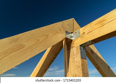 New residential construction home framing and installation of wooden beams at the roof truss system of the house against a blue sky.