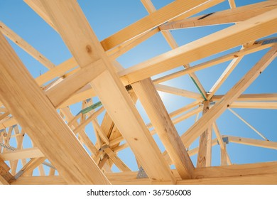 New residential construction home framing against a blue sky.Selective focus
