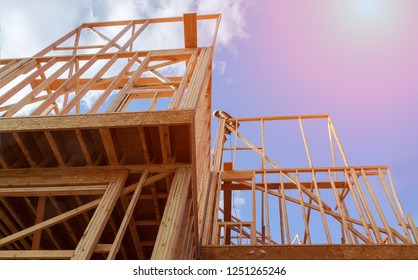 New residential construction house framing against a blue sky.