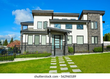 New residential house with concrete tile pathway over front yard lawn and metal fence in front